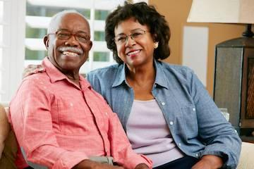 Older couple smiling wearing dental implants in Eagan MN